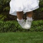 Hispanic girl jumping on grass — Stock Photo