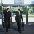 Businessmen entering building - Stock Photo