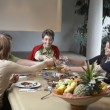 Family toasting at dinner table - Foto Stock