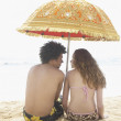 Photo: Rear view of couple sitting on beach underneath umbrella