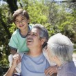Hispanic grandparents with grandson outdoors — Stock Photo #13233916