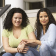Hispanic sisters sitting on the porch holding hands — Foto de Stock