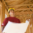 Stock Photo: Male construction worker holding blueprints inside construction site