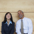Two co-workers sitting and laughing - Stockfoto