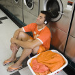 Man sitting on floor listening to music in laundromat — Stockfoto