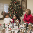 Hispanic mother and daughter playing with Christmas village — Stock Photo #13234092
