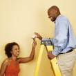 Couple with light bulb on ladder - Stock Photo