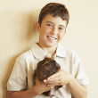 Stock Photo: Hispanic boy holding guinepig