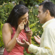 Hispanic woman appraising engagement ring in front of man - Stock Photo