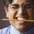 Businessman holding a pencil between his teeth — Stockfoto