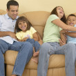 Family tickling each other on the sofa — Stock Photo