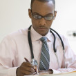 Male doctor writing notes — Stock Photo