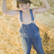 Stock Photo: Young boy wearing overalls and flexing muscles in hay