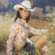 Young woman in cowboy outfit sitting in long grass — Stock Photo