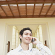 Man talking on cell phone at hotel entrance  — Stock Photo
