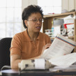 Businesswoman reading papers at her desk — Stock Photo