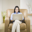 Stock Photo: Pacific Islander womusing laptop in armchair