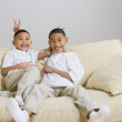 Indian brothers being silly on sofa - Stock Photo