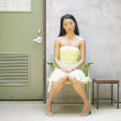 Woman sitting in chair near door — Stock Photo