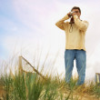 Man standing on sand dune taking photograph — Stock Photo