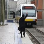 Businessman waving down a train — Stock Photo