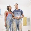 Portrait of couple in overalls painting - Stockfoto