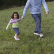 Senior man and granddaughter walking together - Stock Photo