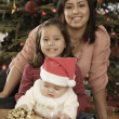 Hispanic mother and children in front of Christmas tree - Stok fotoraf