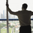 Rear view of businessman looking out office window — Stock Photo