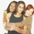 Studio shot of man being hugged by two women - Stockfoto
