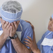 Indian female doctor consoling male doctor - Stock Photo