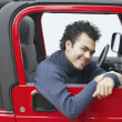 Young man riding in a Jeep — Stock Photo