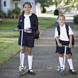 Portrait of sisters wearing uniforms on scooters - Stock Photo