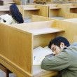 Male college student napping in library — Stok fotoğraf