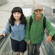 Young couple riding escalator - Stock Photo