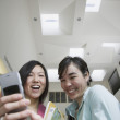 Two female Asian teenagers with cell phone — Stock Photo