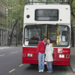 Asian couple hugging in front of tour bus in London — Stok fotoğraf