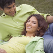 Portrait of couple relaxing on grass — Stock Photo