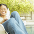 Young woman sitting on a chair outdoors smiling — Stock Photo