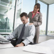 Stock Photo: Hispanic businesswomgiving Hispanic businessmshoulder massage in his cubicle