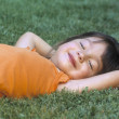 Young girl laying in the grass - Stock Photo