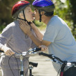 Senior couple kissing with bicycles — Stock Photo