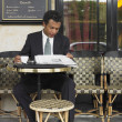Businessman reading newspaper at outdoor cafe — Stock Photo