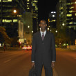 African businessman in urban setting at night  — Stock Photo