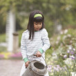 Asian girl using watering can in garden - Stock Photo