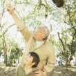 Hispanic grandfather and grandson in woods - Stock Photo