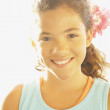 Portrait of Hispanic girl in sunlight - Stock Photo