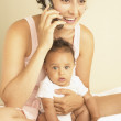 Young mother talking on phone with baby in arms — Stock Photo