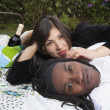 Portrait of couple laying on blanket with picnic basket — Stock Photo