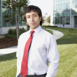 Hispanic businessman in front of office buildings - Stock Photo